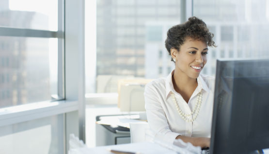 Businesswoman working with managed IT services at desk in office